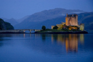 A typical photo of Eileen Donan castle, taken at dusk with the castle lit up and reflected in the water.