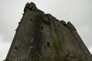 A close-up photo of the castle, large and looming, against a grey sky.