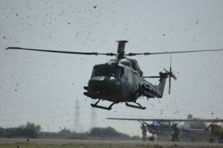 a Lynx helicopter with grass being blown about